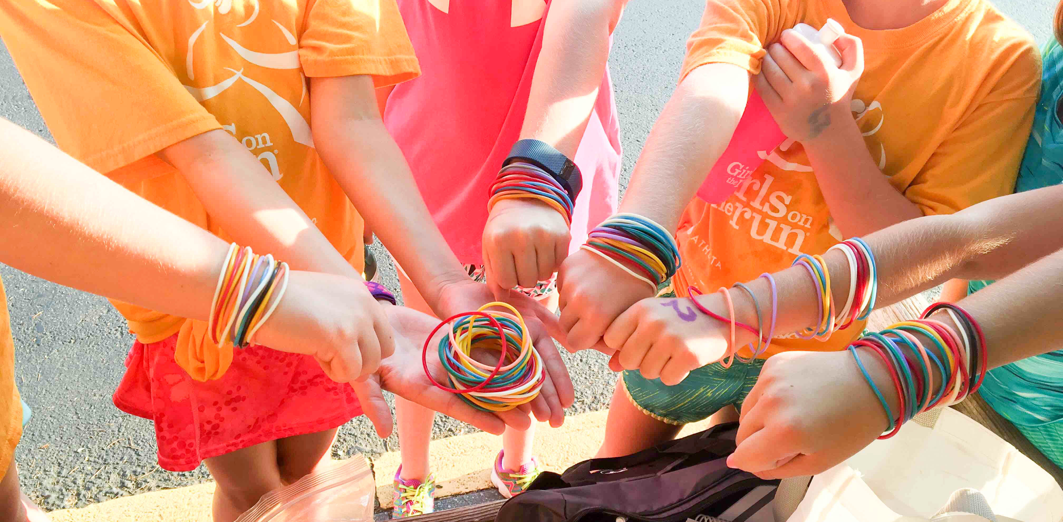 Girls on the Run girls wearing jelly bracelets and putting their hands together