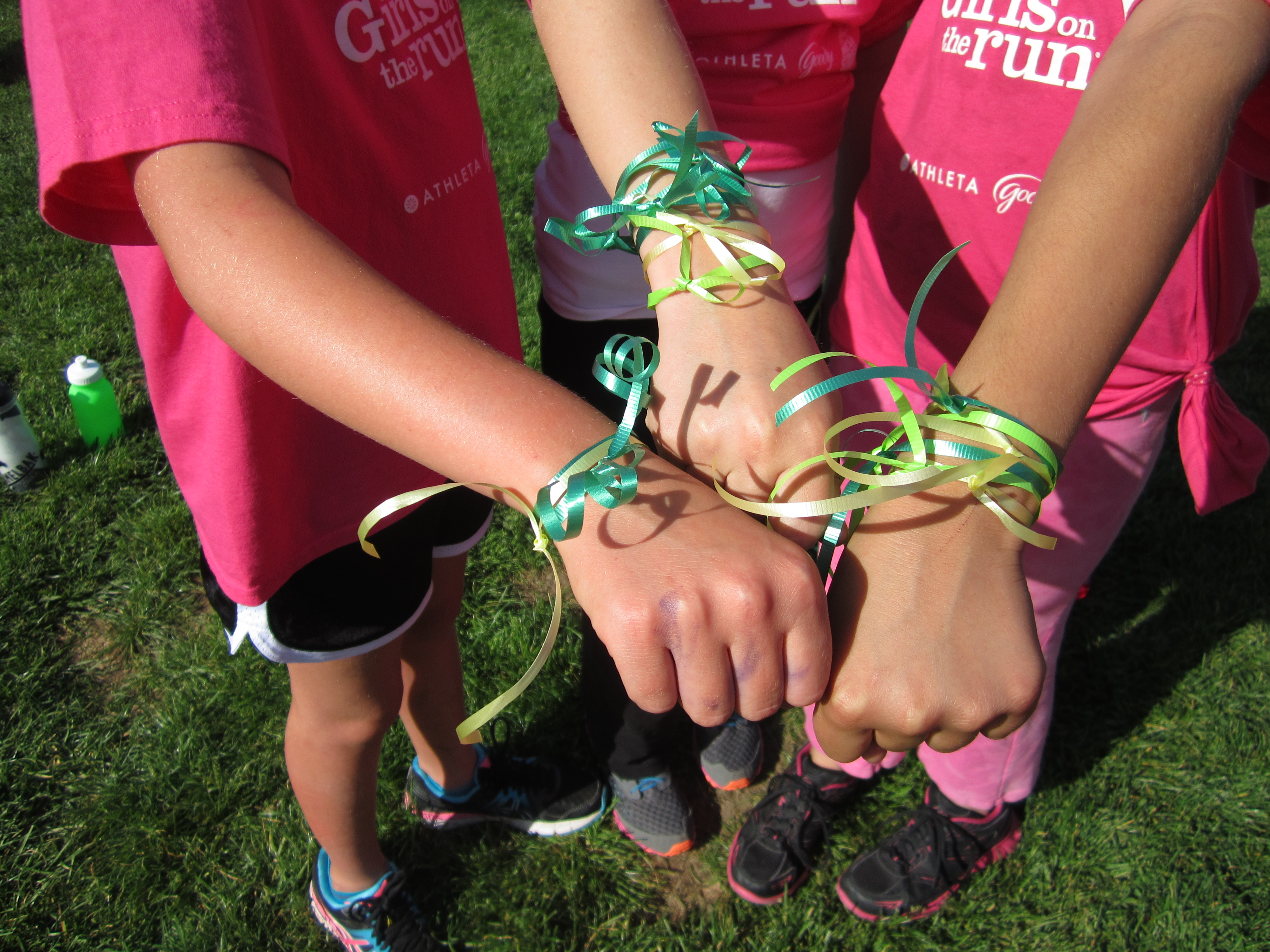 Girls on the Run girls wearing ribbon on their wrists and putting their hands together